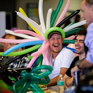 male student laughing wearing balloon hat