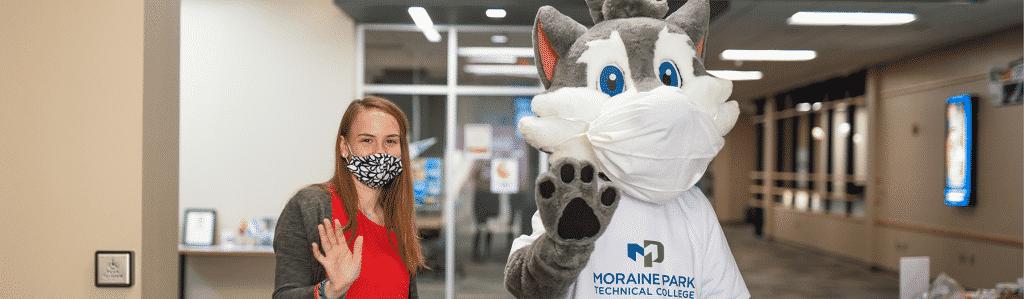 student and mascot wearing masks waving
