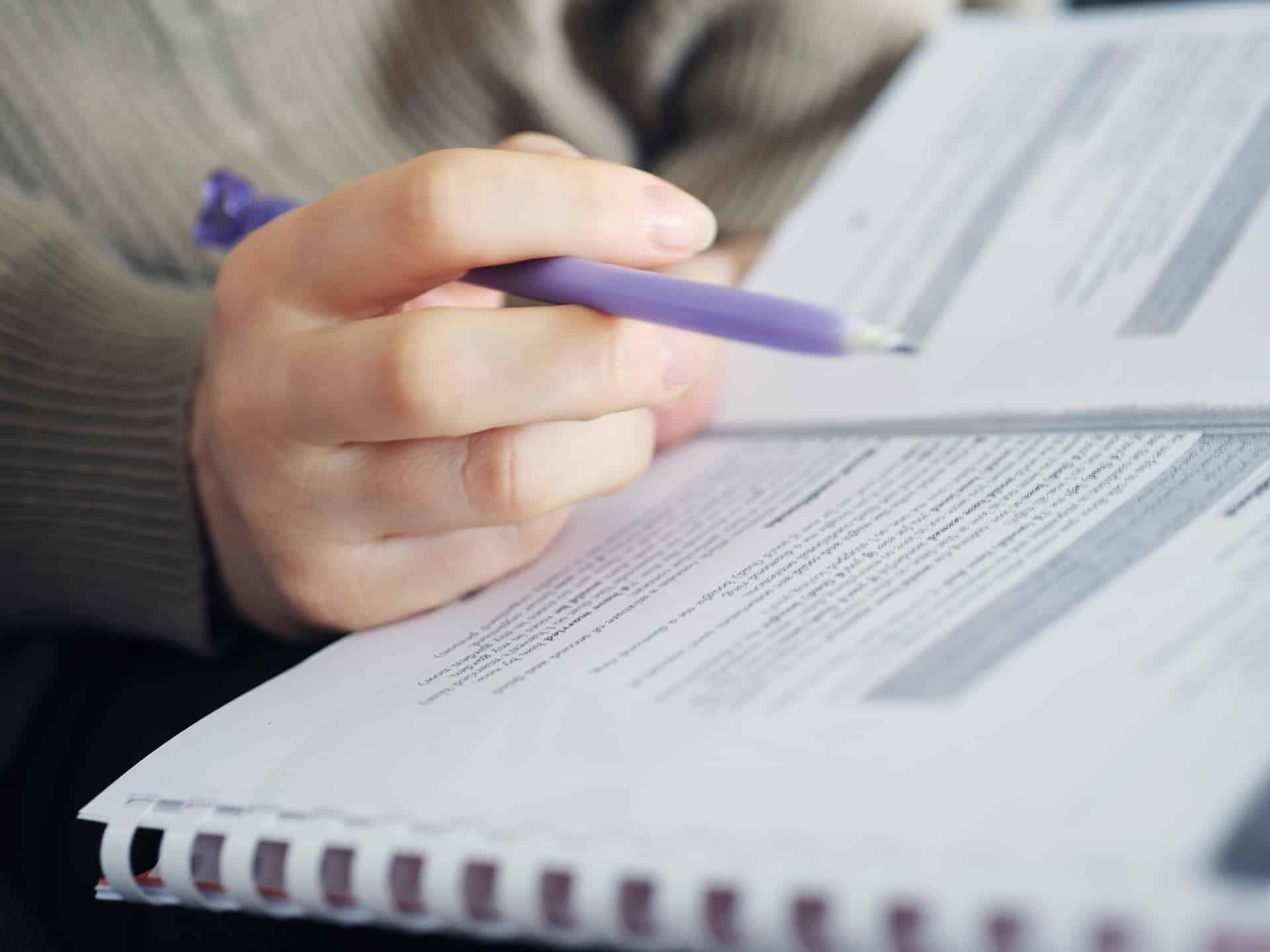 hand holding pen doing paperwork