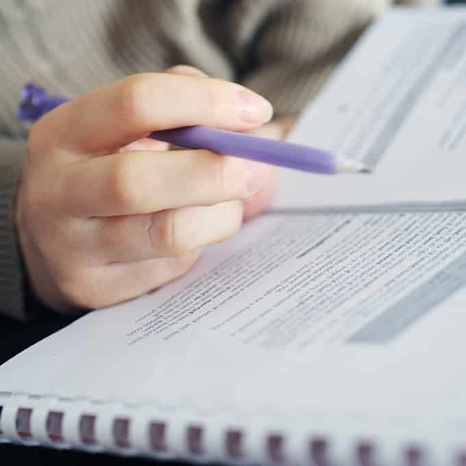 close up of hand holding pen above paperwork